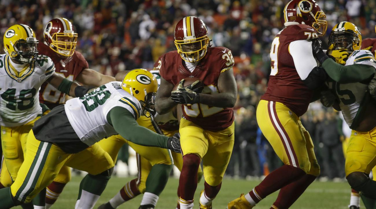 Washington Redskins running back Rob Kelley (32) runs past Green Bay Packers defensive end Letroy Guion (98) for a touchdown during the second half of an NFL football game in Landover, Md., Sunday, Nov. 20, 2016. The Redskins defeated the Packer 42-24. (A