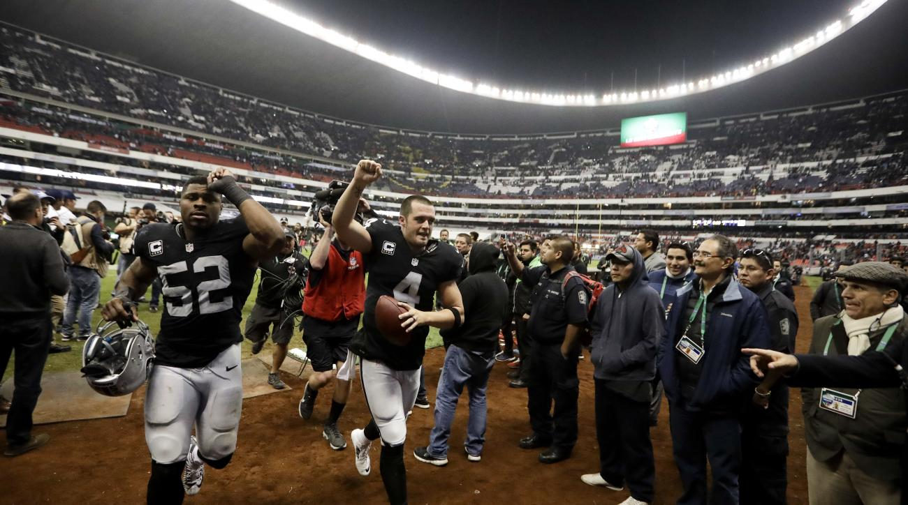 Oakland Raiders quarterback Derek Carr, center, and defensive end Khalil Mack (52) celebrate after their NFL football game against the Houston Texans Monday, Nov. 21, 2016, in Mexico City. The Raiders won, 27-20. (AP Photo/Eduardo Verdugo)