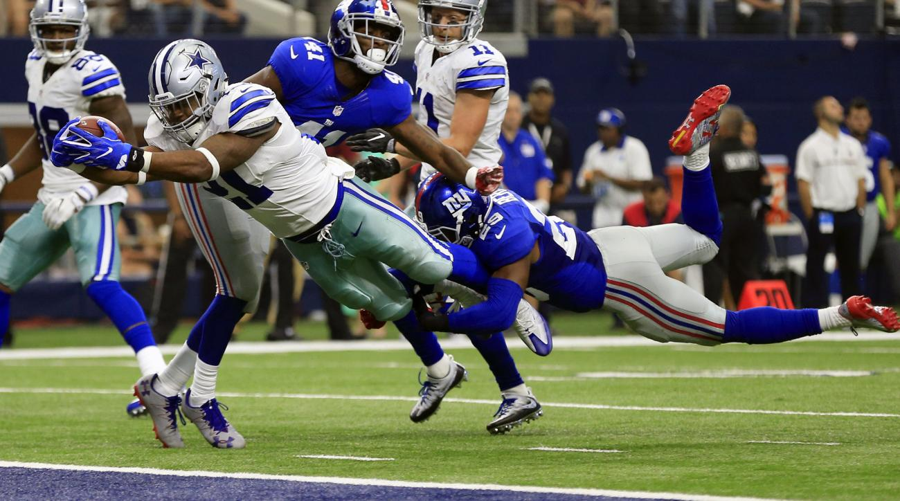 FILE - In this Sept. 11, 2016, file photo, Dallas Cowboys running back Ezekiel Elliott (21) leaps into the end zone after getting past New York Giants cornerback Dominique Rodgers-Cromartie (41) and Nat Berhe (29) for his first career touchdown in the sec