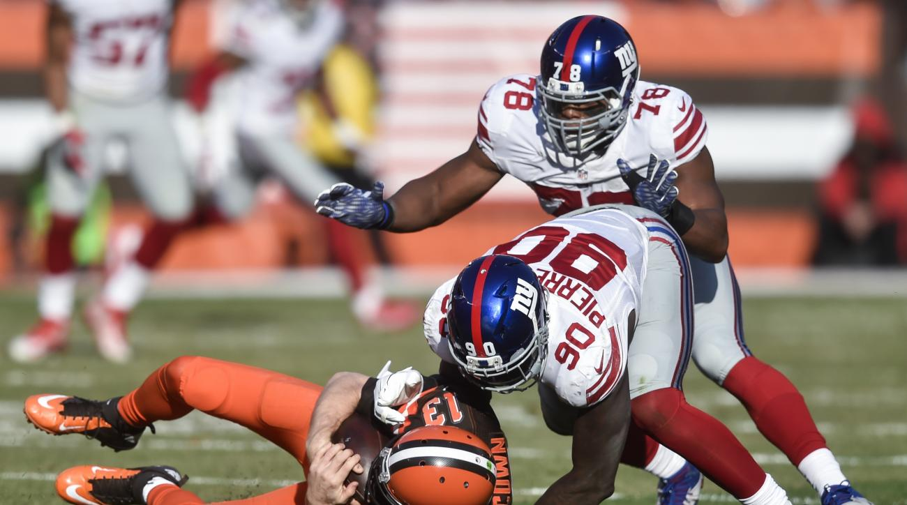 Cleveland Browns quarterback Josh McCown (13) is sacked by New York Giants defensive end Jason Pierre-Paul (90) alongside defensive end Romeo Okwara (78) in the first half of an NFL football game, Sunday, Nov. 27, 2016, in Cleveland. (AP Photo/David Richa