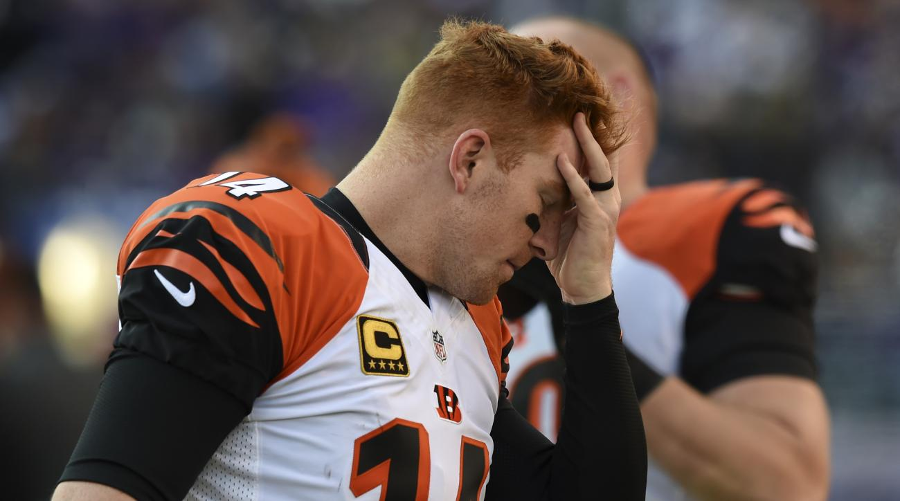 Cincinnati Bengals quarterback Andy Dalton (14) holds his head as he walks along the sidelines during the second half of an NFL football game against the Baltimore Ravens in Baltimore, Sunday, Nov. 27, 2016. (AP Photo/Gail Burton)