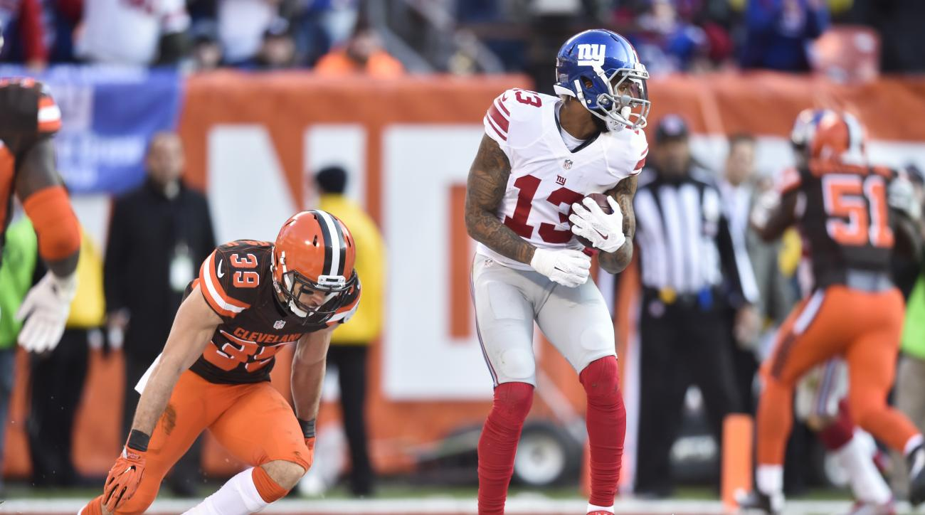 New York Giants wide receiver Odell Beckham (13) scores a touchdown against Cleveland Browns defensive back Ed Reynolds (39) in the second half of an NFL football game, Sunday, Nov. 27, 2016, in Cleveland. (AP Photo/David Richard)