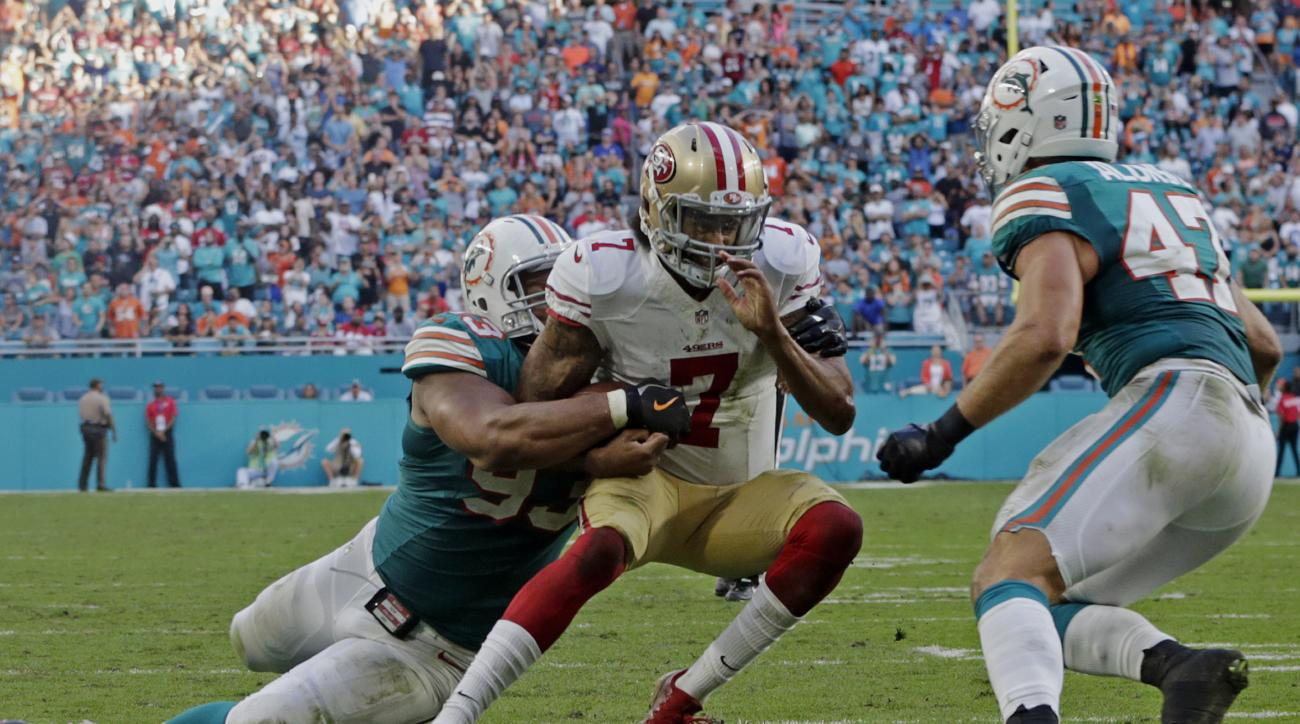 San Francisco 49ers quarterback Colin Kaepernick (7) is tackled by Miami Dolphins defensive tackle Ndamukong Suh (93) near the end zone, during the second half of an NFL football game, Sunday, Nov. 27, 2016, in Miami Gardens, Fla. To the right is Miami Do