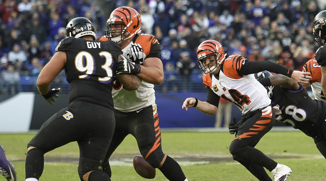 Cincinnati Bengals quarterback Andy Dalton (14) chases a fumbled ball after being sacked by Baltimore Ravens outside linebacker Elvis Dumervil (58) during the second half of an NFL football game against the Baltimore Ravens in Baltimore, Sunday, Nov. 27,