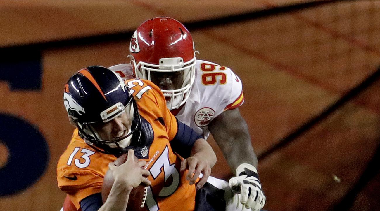Denver Broncos quarterback Trevor Siemian (13) dives as Kansas City Chiefs defensive tackle Rakeem Nunez-Roches (99) pursues during the second half of an NFL football game, Sunday, Nov. 27, 2016, in Denver. (AP Photo/Jack Dempsey)