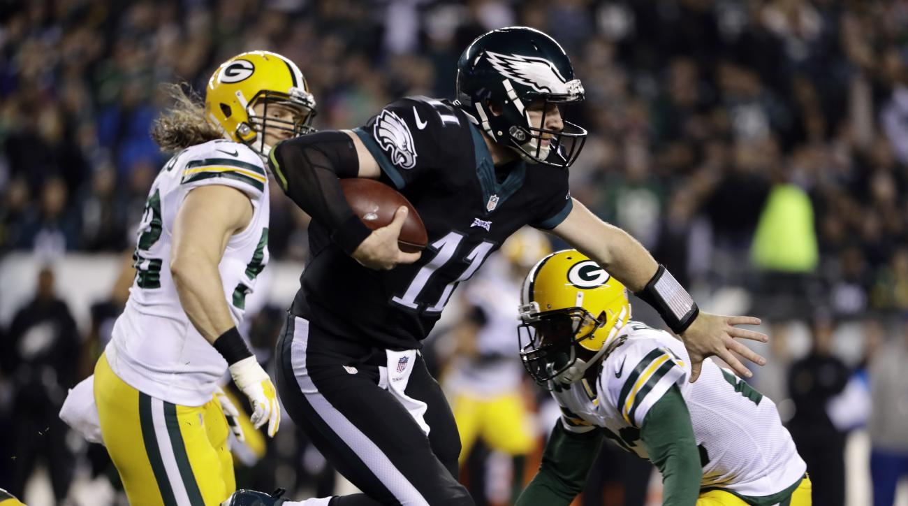 Philadelphia Eagles' Carson Wentz, center, scrambles past Green Bay Packers' Damarious Randall, right, and Clay Matthews during the first half of an NFL football game, Monday, Nov. 28, 2016, in Philadelphia. (AP Photo/Matt Rourke)
