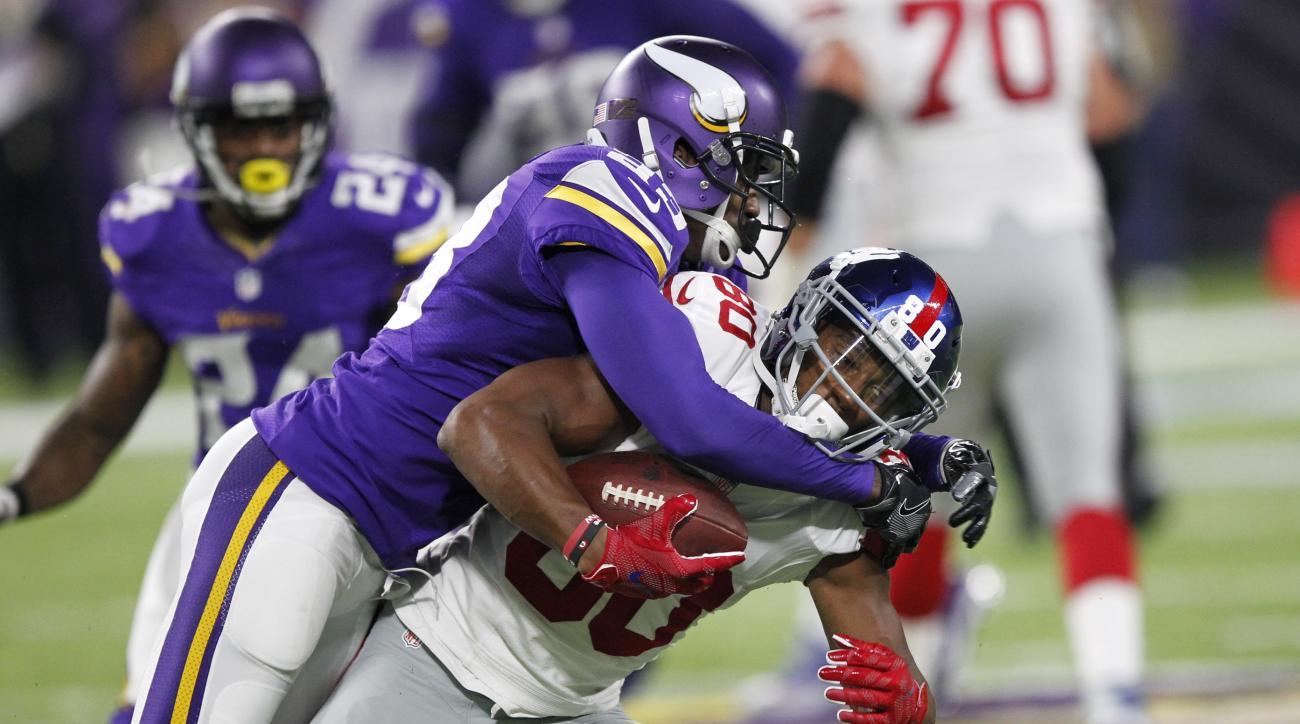 FILE - In this Oct. 3, 2016, file photo, Minnesota Vikings cornerback Terence Newman, left, tackles New York Giants wide receiver Victor Cruz during the first half of an NFL football game, in Minneapolis.  Thirteen years after the Dallas Cowboys drafted T