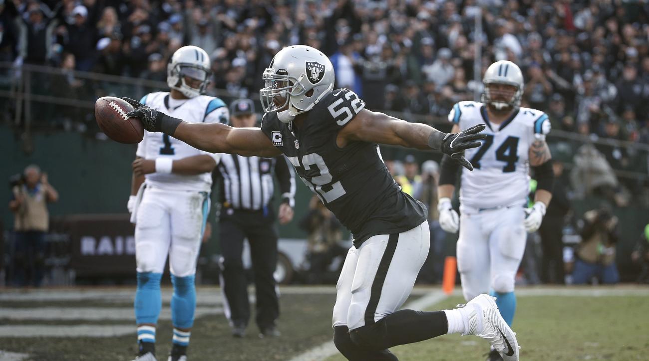 FILE - In this Sunday, Nov. 27, 2016, file photo, Oakland Raiders defensive end Khalil Mack (52) scores a touchdown after intercepting a pass by Carolina Panthers quarterback Cam Newton, left rear, during the first half of an NFL football game in Oakland,