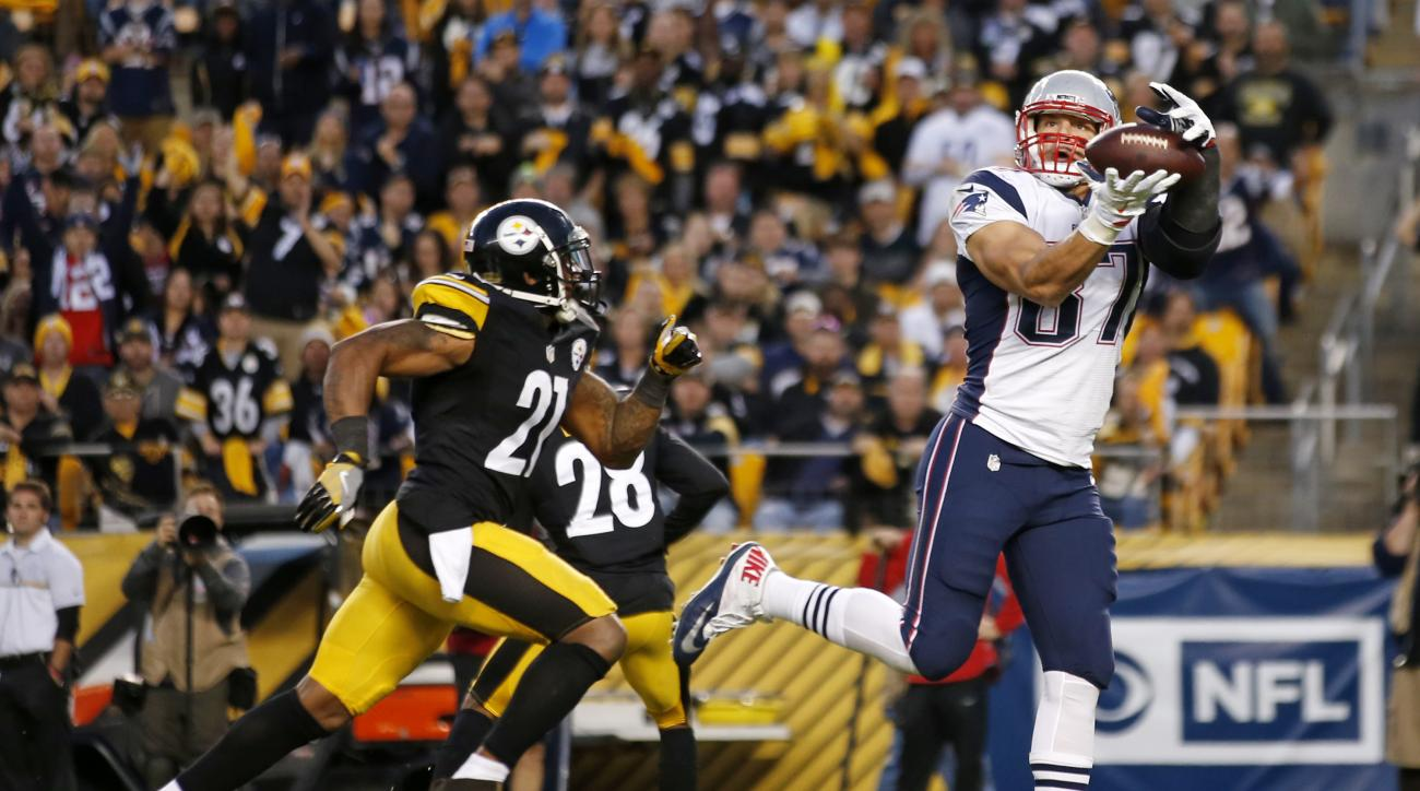 FILE - In this Oct. 23, 2016, file photo, New England Patriots tight end Rob Gronkowski (87) takes a pass from quarterback Tom Brady behind Pittsburgh Steelers strong safety Robert Golden (21) for a touchdown during the second half of an NFL football game