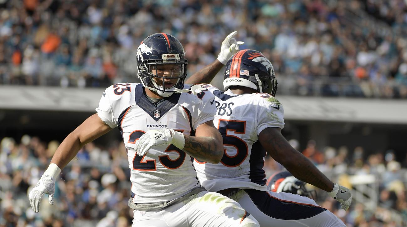 Denver Broncos running back Devontae Booker, left, celebrates his 6-yard touchdown run against the Jacksonville Jaguars with teammate running back Kapri Bibbs during the first half of an NFL football game in Jacksonville, Fla., Sunday, Dec. 4, 2016. (AP P