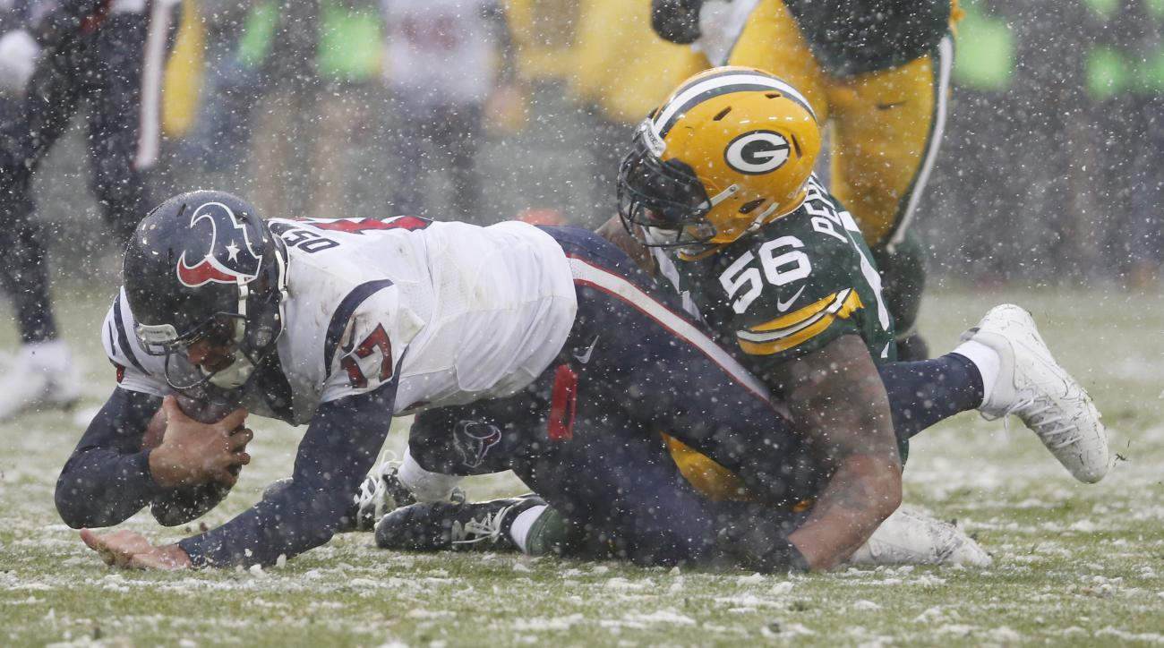 Houston Texans quarterback Brock Osweiler is sacked by Green Bay Packers' Julius Peppers during the first half of an NFL football game Sunday, Dec. 4, 2016, in Green Bay, Wis. (AP Photo/Mike Roemer)