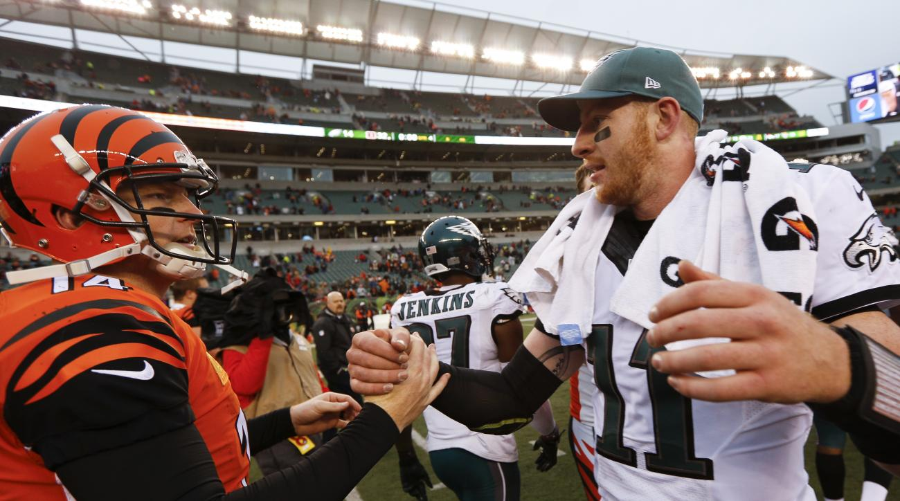 Cincinnati Bengals quarterback Andy Dalton (14) and Philadelphia Eagles quarterback Carson Wentz (11) meet on the field after an NFL football game, Sunday, Dec. 4, 2016, in Cincinnati. (AP Photo/Frank Victores)