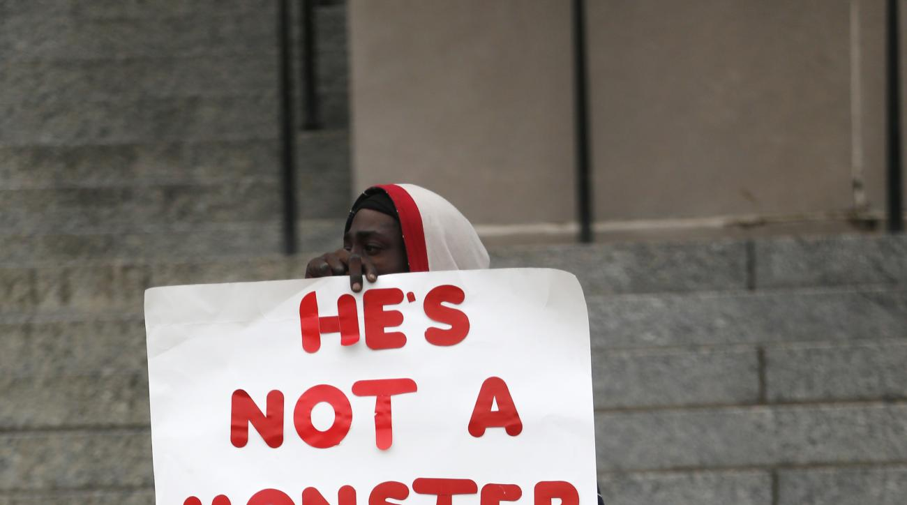 A supporter of Cardell Hayes holds signs outside Orleans Parish Criminal District Court, during a break in Hayes' murder trial in New Orleans, Wednesday, Dec. 7, 2016. Hayes killed former NFL New Orleans Saints player Will Smith in a road rage incident, i
