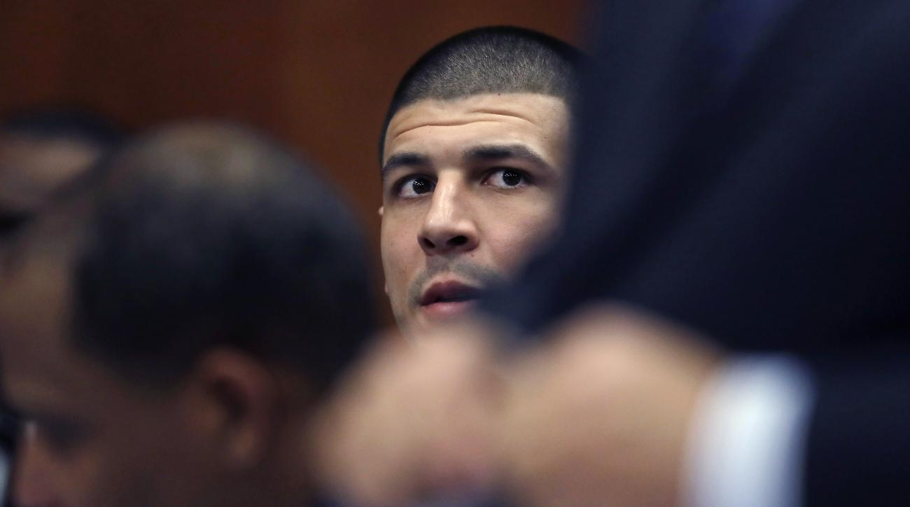 Former New England Patriots NFL football player Aaron Hernandez, center, sits with his defense team during a court appearance at Suffolk Superior Court in Boston, Wednesday, Dec. 7, 2016. Hernandez, who is serving a life sentence for the 2013 killing of O
