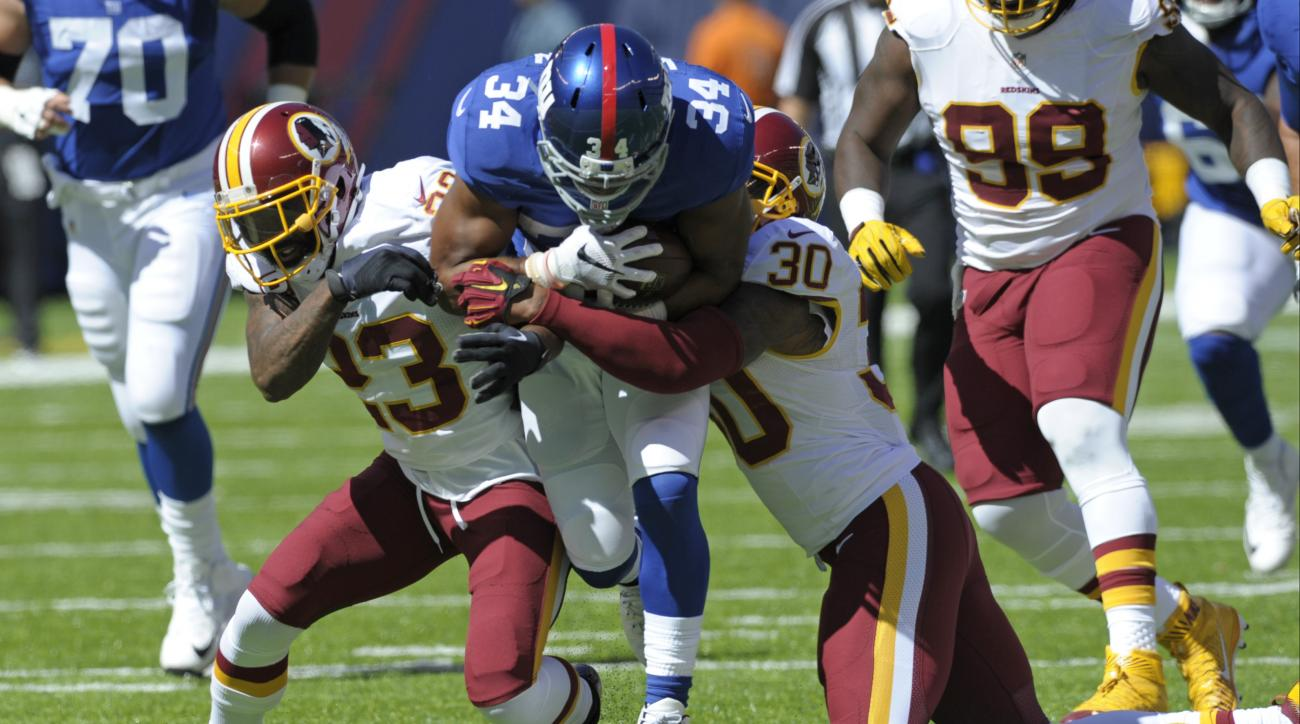 In this photo taken Sept. 25, 2016, Washington Redskins DeAngelo Hall (23) and David Bruton (30) tackle New York Giants running back Shane Vereen (34) during the first half of an NFL football game in East Rutherford, N.J. Redskins coach Jay Gruden says sa