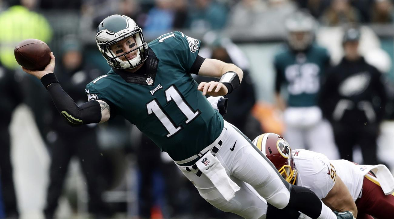 Philadelphia Eagles' Carson Wentz, left, is tackled by Washington Redskins' Ryan Kerrigan during the first half of an NFL football game Sunday, Dec. 11, 2016, in Philadelphia. (AP Photo/Matt Rourke)