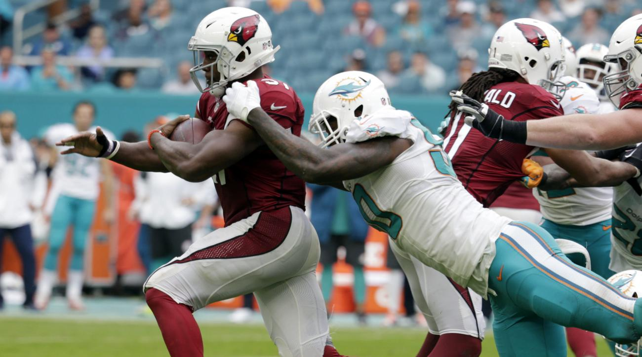 Miami Dolphins defensive end Andre Branch (50) tackles Arizona Cardinals running back David Johnson (31), during the second half of an NFL football game, Sunday, Dec. 11, 2016, in Miami Gardens, Fla. (AP Photo/Lynne Sladky)