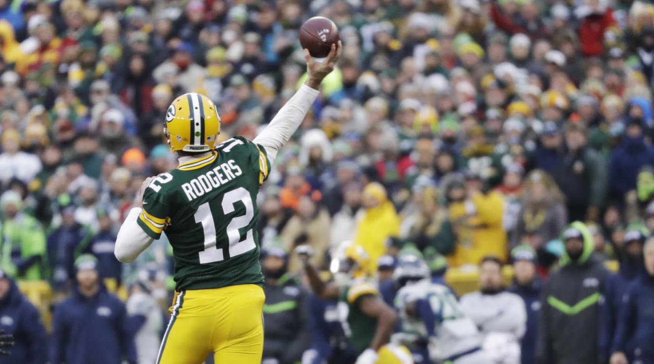 Green Bay Packers' Aaron Rodgers throws a touchdown pass to Davante Adams during the first half of an NFL football game against the Seattle Seahawks Sunday, Dec. 11, 2016, in Green Bay, Wis. (AP Photo/Morry Gash)
