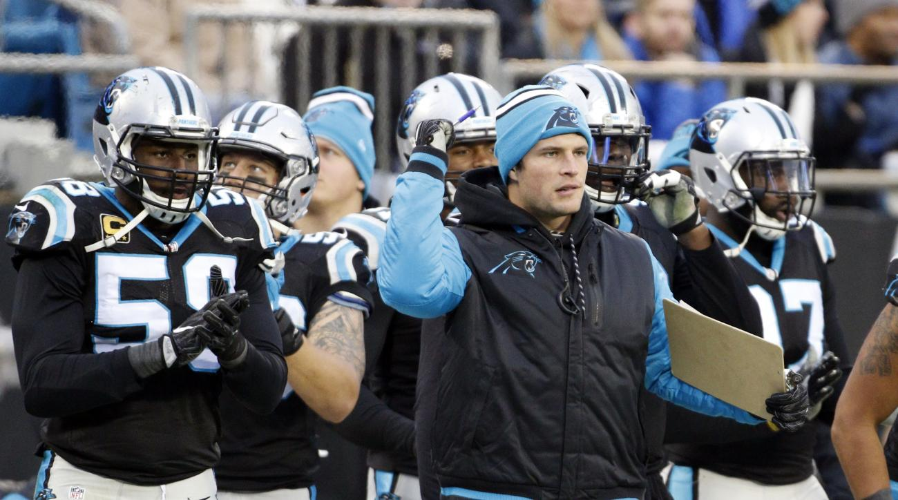 Carolina Panthers' Luke Kuechly, center, cheers on his team in the second half of an NFL football game against the San Diego Chargers in Charlotte, N.C., Sunday, Dec. 11, 2016. (AP Photo/Bob Leverone)