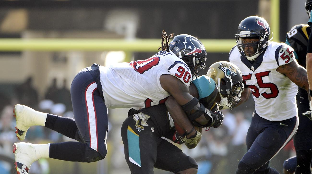 FILE - In this Nov. 13, 2016, file photo, Jacksonville Jaguars running back T.J. Yeldon, center, is tackled by Houston Texans defensive end Jadeveon Clowney (90) after a short gain during the second half of an NFL football game in Jacksonville, Fla. Clown