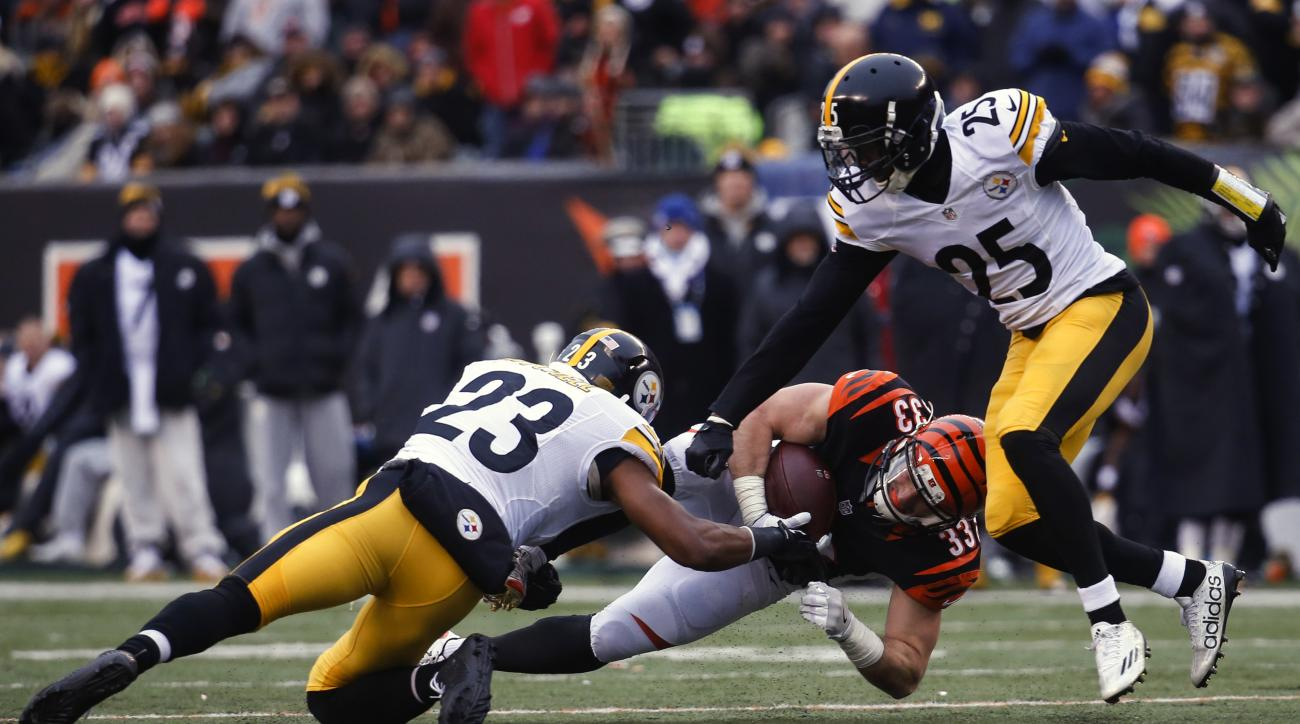 Cincinnati Bengals running back Rex Burkhead (33) dives for yardage against Pittsburgh Steelers free safety Mike Mitchell (23) and cornerback Artie Burns (25) in the first half of an NFL football game, Sunday, Dec. 18, 2016, in Cincinnati. (AP Photo/Frank