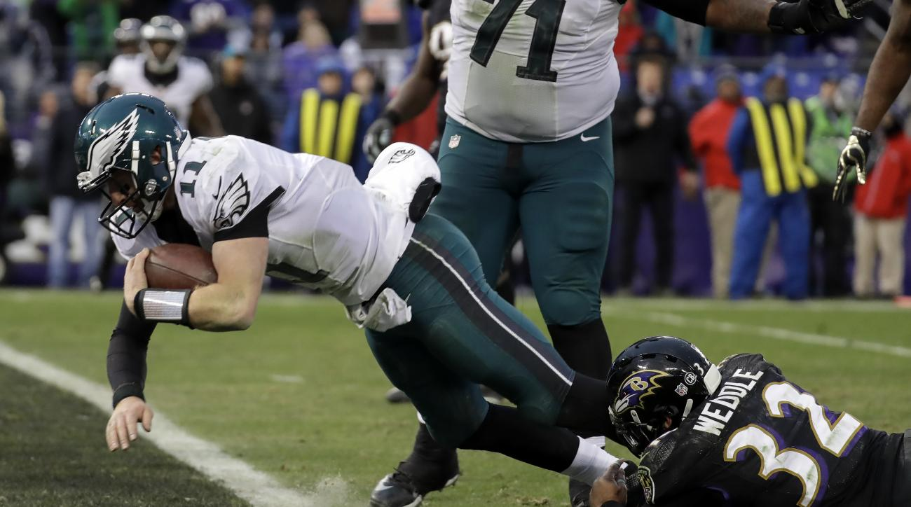 Philadelphia Eagles quarterback Carson Wentz (11) dives into the end zone on a quarterback keeper as Baltimore Ravens strong safety Eric Weddle (32) hangs on during the second half of an NFL football game in Baltimore, Sunday, Dec. 18, 2016. The Ravens de