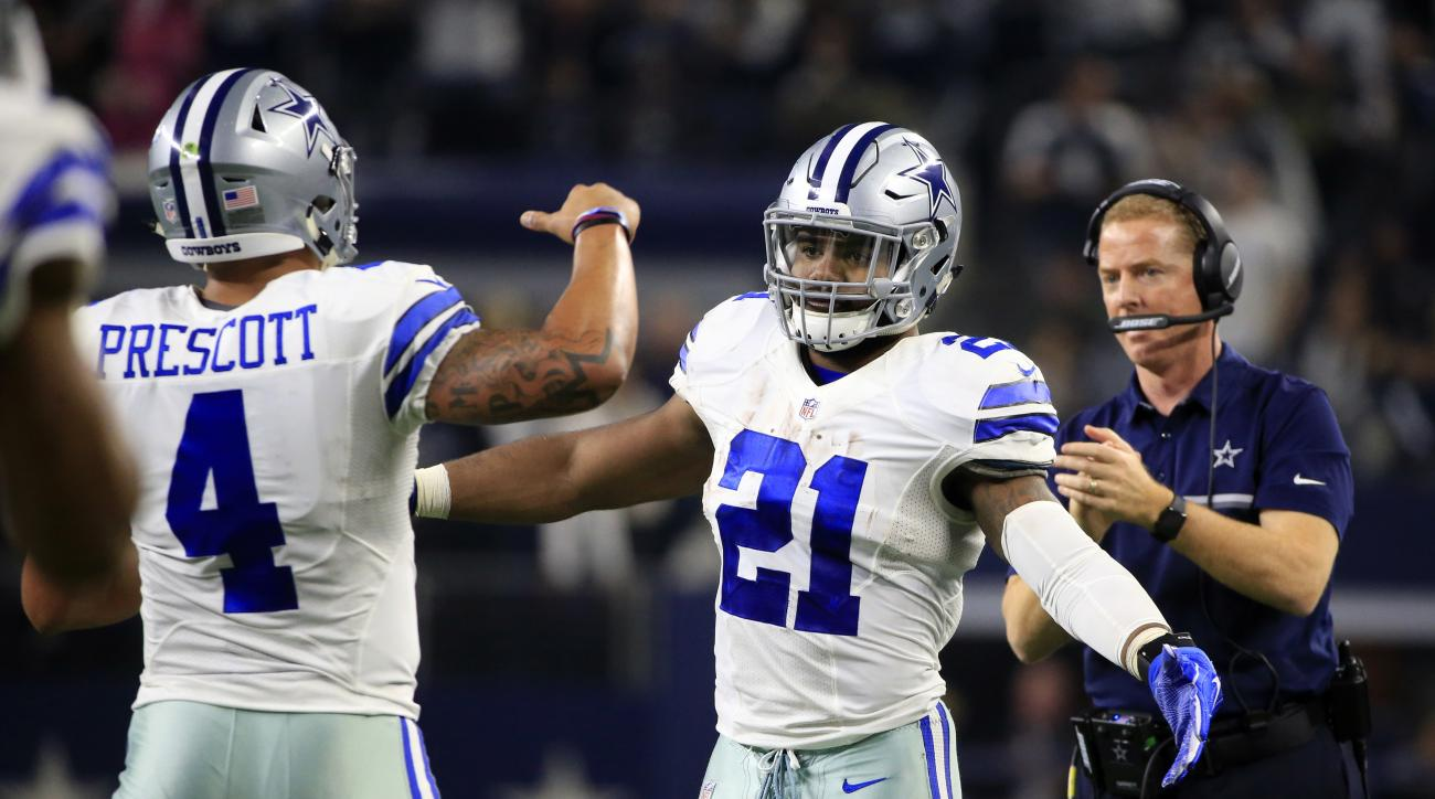 Dallas Cowboys' Dak Prescott (4) is congratulated on his touchdown run by Ezekiel Elliott (21) in the first half of an NFL football game against the Tampa Bay Buccaneers as head coach Jason Garrett, right, watches, , Sunday, Dec. 18, 2016, in Arlington, T