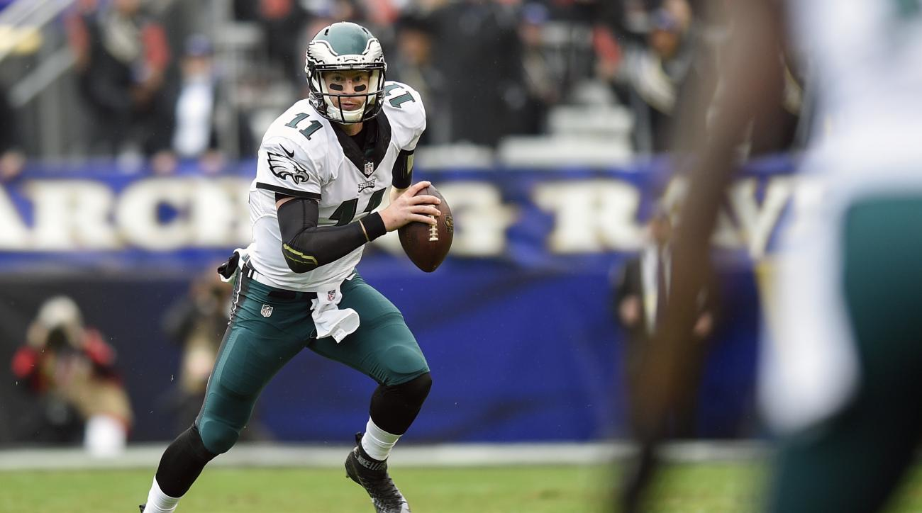 FILE - In this Dec. 18, 2016, file photo, Philadelphia Eagles quarterback Carson Wentz (11) scrambles with the ball during the first half of an NFL football game against the Baltimore Ravens in Baltimore. There's plenty at stake when the Giants (10-4) vis