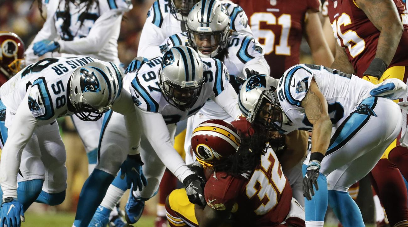 In this Monday, Dec. 19, 2016 photo, Washington Redskins running back Rob Kelley (32) is overwhelmed by the Carolina Panthers defense during the second half of an NFL football game in Landover, Md.   With their playoff hopes at stake, the Redskins want to