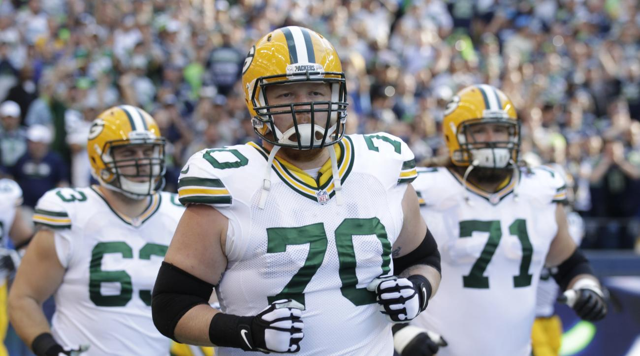 FILE - In this Sept. 4, 2014, file photo, Green Bay Packers guard T.J. Lang (70), center Corey Linsley, left, and guard Josh Sitton take the field before an NFL football game against the Seattle Seahawks in Seattle. A bright green folder waiting for  Lang