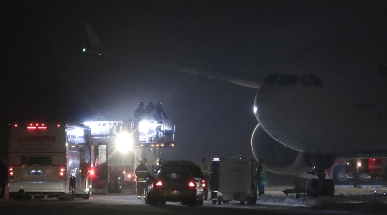 Players, coaches and staff from the Minnesota Vikings are taken off a plane in small groups at Appleton International Airport on Friday, Dec. 23, 2016, in Appleton, Wis. The NFL football team' plane slid off a runway and became stuck in the grass, leaving