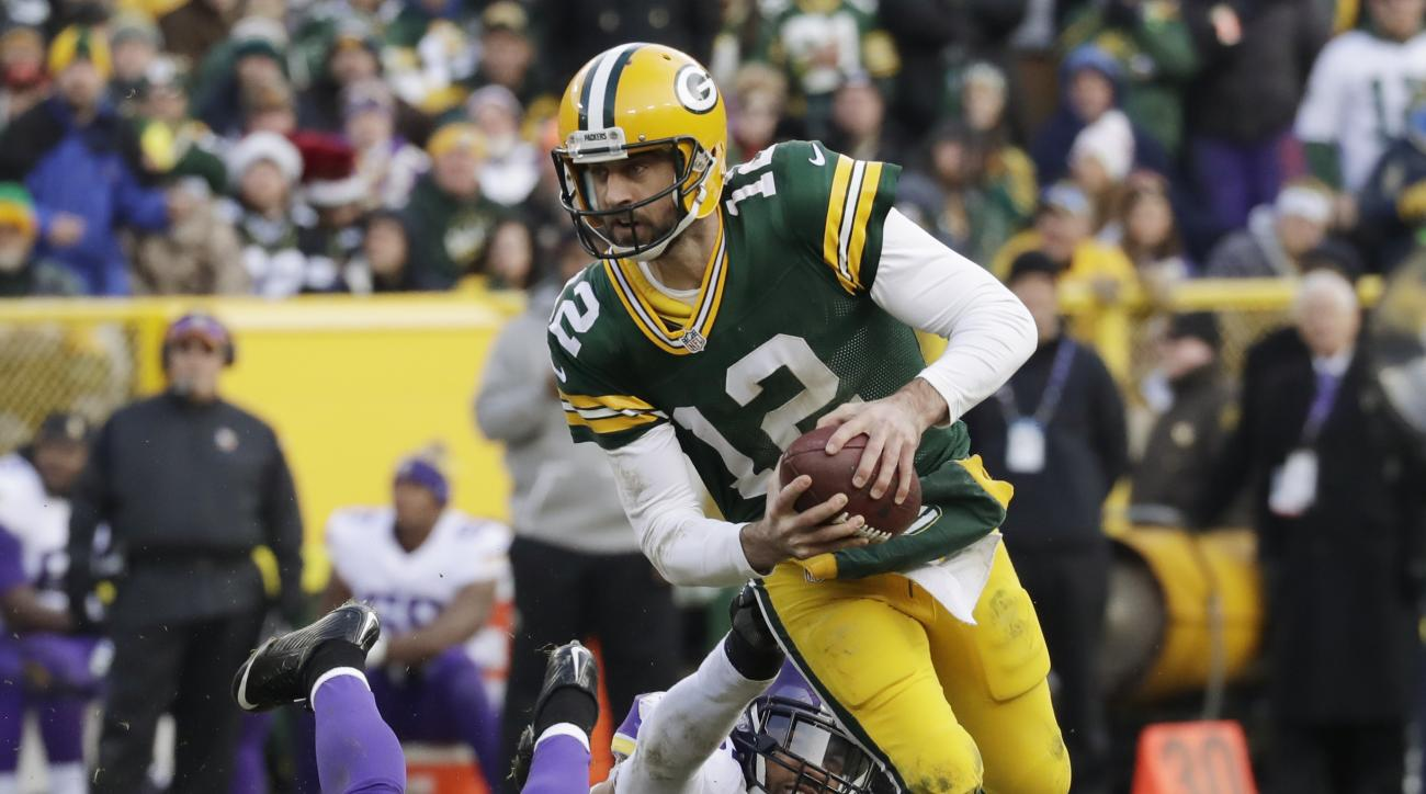 Green Bay Packers' Aaron Rodgers scrambles away from Minnesota Vikings' Anthony Barr during the second half of an NFL football game Saturday, Dec. 24, 2016, in Green Bay, Wis. (AP Photo/Morry Gash)