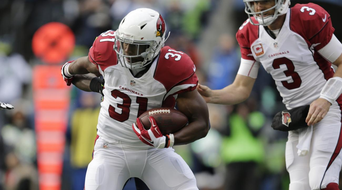 Arizona Cardinals' David Johnson (31) carries after a handoff from quarterback Carson Palmer (3) in the first half of an NFL football game against the Seattle Seahawks, Saturday, Dec. 24, 2016, in Seattle. (AP Photo/John Froschauer)