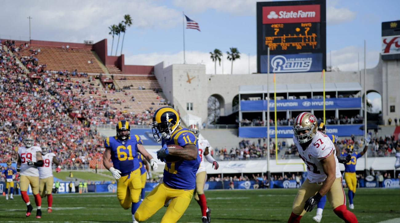 Los Angeles Rams wide receiver Tavon Austin scores as San Francisco 49ers inside linebacker Michael Wilhoite looks on during the first half of an NFL football game, Saturday, Dec. 24, 2016, in Los Angeles. (AP Photo/Jae C. Hong)