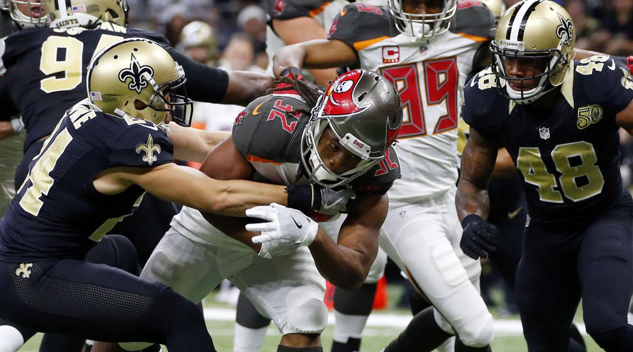 Tampa Bay Buccaneers running back Jacquizz Rodgers (32) carries for a touchdown against New Orleans Saints cornerback Sterling Moore and free safety Vonn Bell (48) in the second half of an NFL football game in New Orleans, Saturday, Dec. 24, 2016. (AP Pho