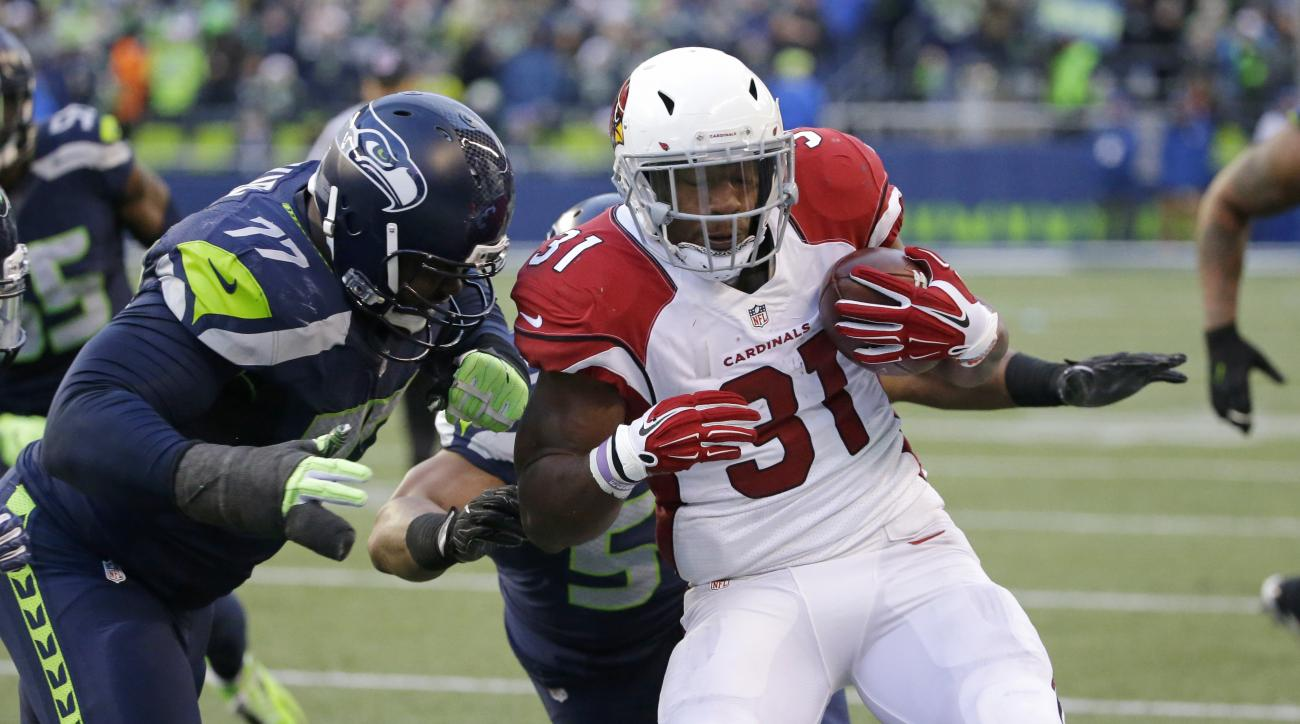 Seattle Seahawks' Ahtyba Rubin, left, and Bobby Wagner tackle Arizona Cardinals' David Johnson on a carry by Johnson in the second half of an NFL football game, Saturday, Dec. 24, 2016, in Seattle. (AP Photo/Ted S. Warren)