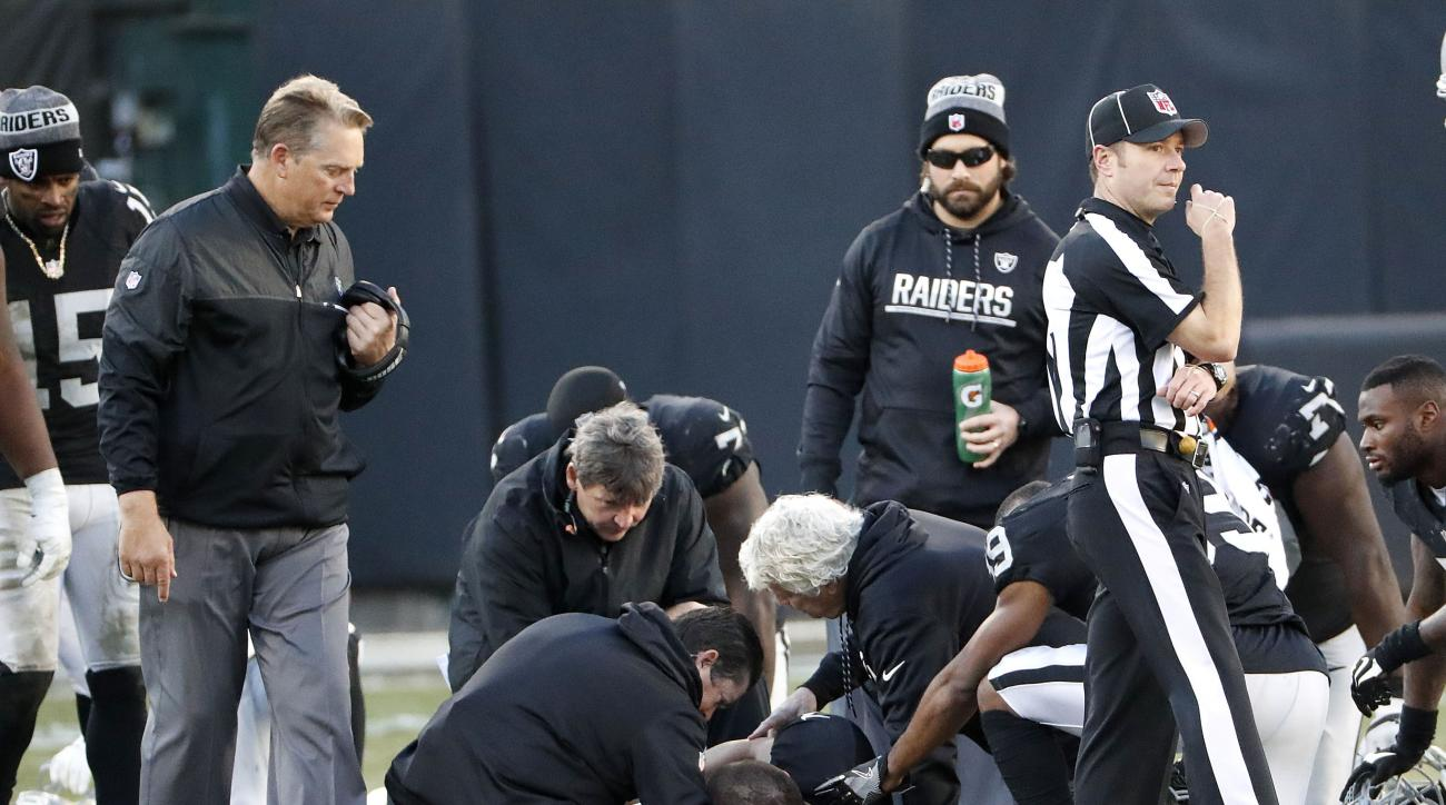 Oakland Raiders head coach Jack Del Rio, left, watches as quarterback Derek Carr, bottom, is tended to by trainers during the second half of an NFL football game against the Indianapolis Colts in Oakland, Calif., Saturday, Dec. 24, 2016. (AP Photo/Tony Av