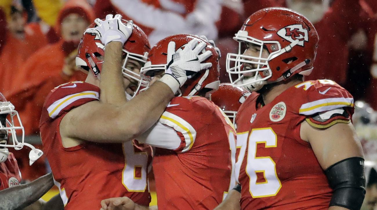 Kansas City Chiefs quarterback Alex Smith, second right, celebrates his touchdown against the Denver Broncos with offensive lineman Mitch Morse, left, and offensive lineman Laurent Duvernay-Tardif (76) during the first half of an NFL football game in Kans