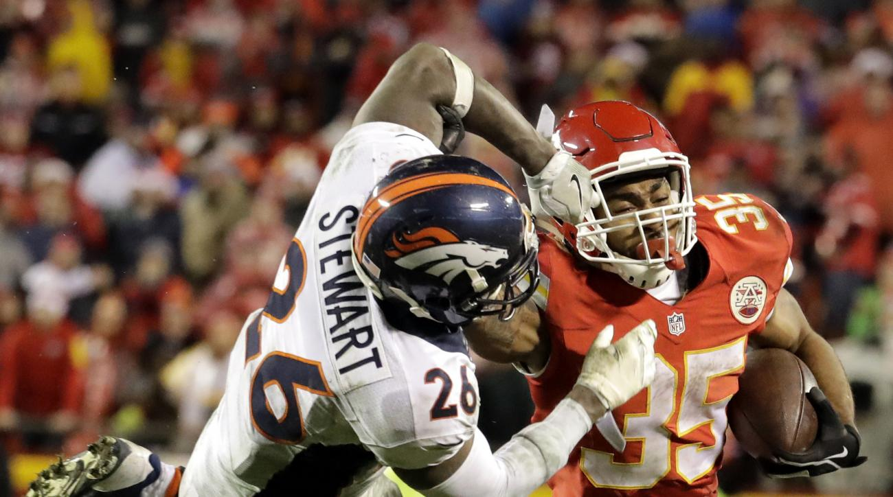 Denver Broncos safety Darian Stewart (26) grabs the face mask of Kansas City Chiefs running back Charcandrick West (35) during the second half of an NFL football game in Kansas City, Mo., Sunday, Dec. 25, 2016. (AP Photo/Charlie Riedel)