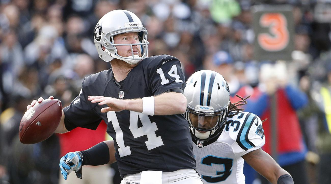 FILE - In this Nov. 27, 2016, file photo, Oakland Raiders quarterback Matt McGloin (14) drops back as Carolina Panthers free safety Tre Boston (33) applies pressure during the second half of an NFL football game in Oakland, Calif. After losing star quarte