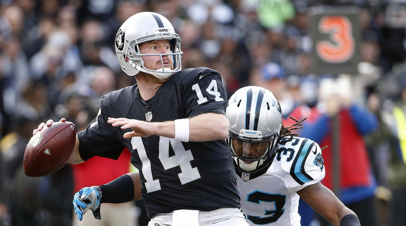 FILE - In this Nov. 27, 2016, file photo, Oakland Raiders quarterback Matt McGloin (14) drops back as Carolina Panthers free safety Tre Boston (33) applies pressure during the second half of an NFL football game in Oakland, Calif. The Raiders are headed t