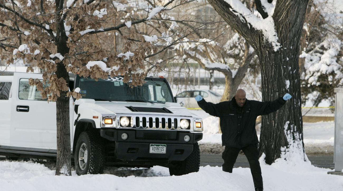 FILE - In this Monday, Jan. 1, 2007, file photo, a Denver Police Department investigator climbs over a snowbank next to a limousine in which Denver Broncos cornerback Darrent Williams was shot and killed in downtown Denver. New Year's Day marks the 10-yea