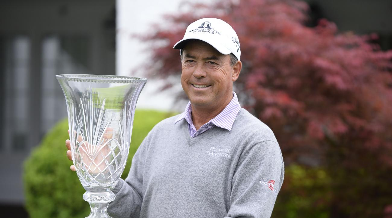 PGA Champions Tour player Olin Browne holds the winner's trophy after rain forced the cancellation of the final round of the Greater Gwinnett Championship golf tournament Sunday, April 19, 2015, in Duluth, Ga. Browne won the shortened event at 12 under af