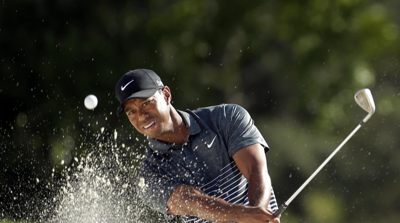 Tiger Woods hits out of a bunker on the 18th hole during the third round of the Masters golf tournament Saturday, April 11, 2015, in Augusta, Ga. (AP Photo/Chris Carlson)