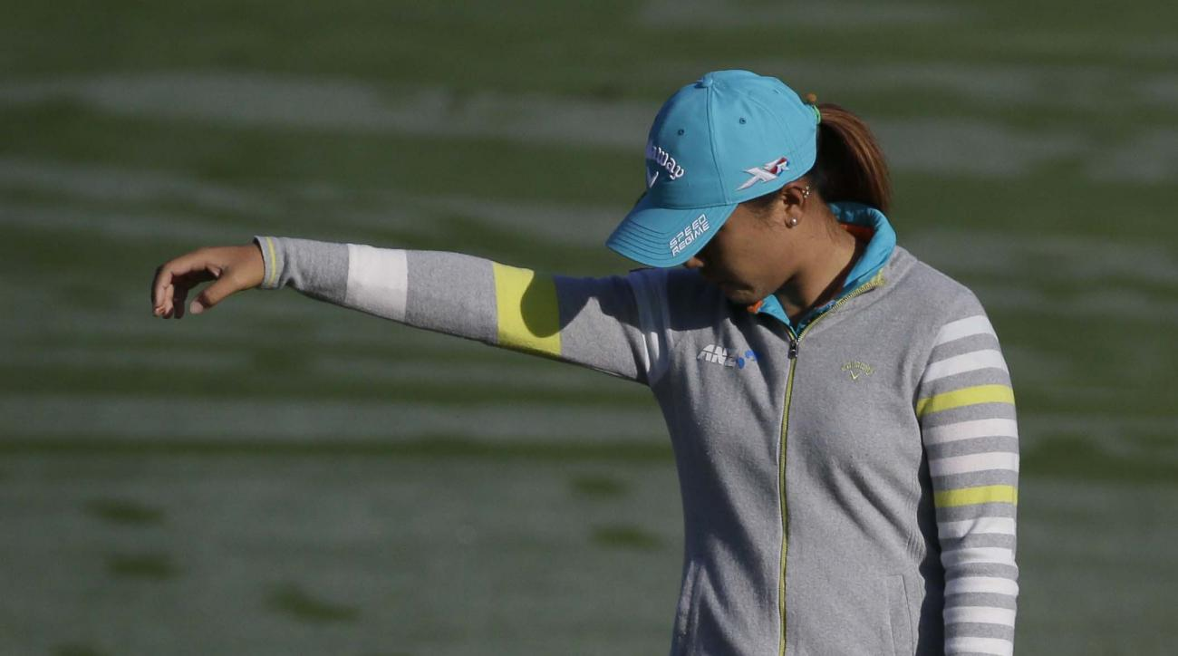 Lydia Ko takes a drop on the first hole,  in soggy grass, during first round play in the LPGA Tour's North Texas Shootout golf tournament, Thursday, April 30, 2015, in Irving, Texas. (AP Photo/LM Otero)