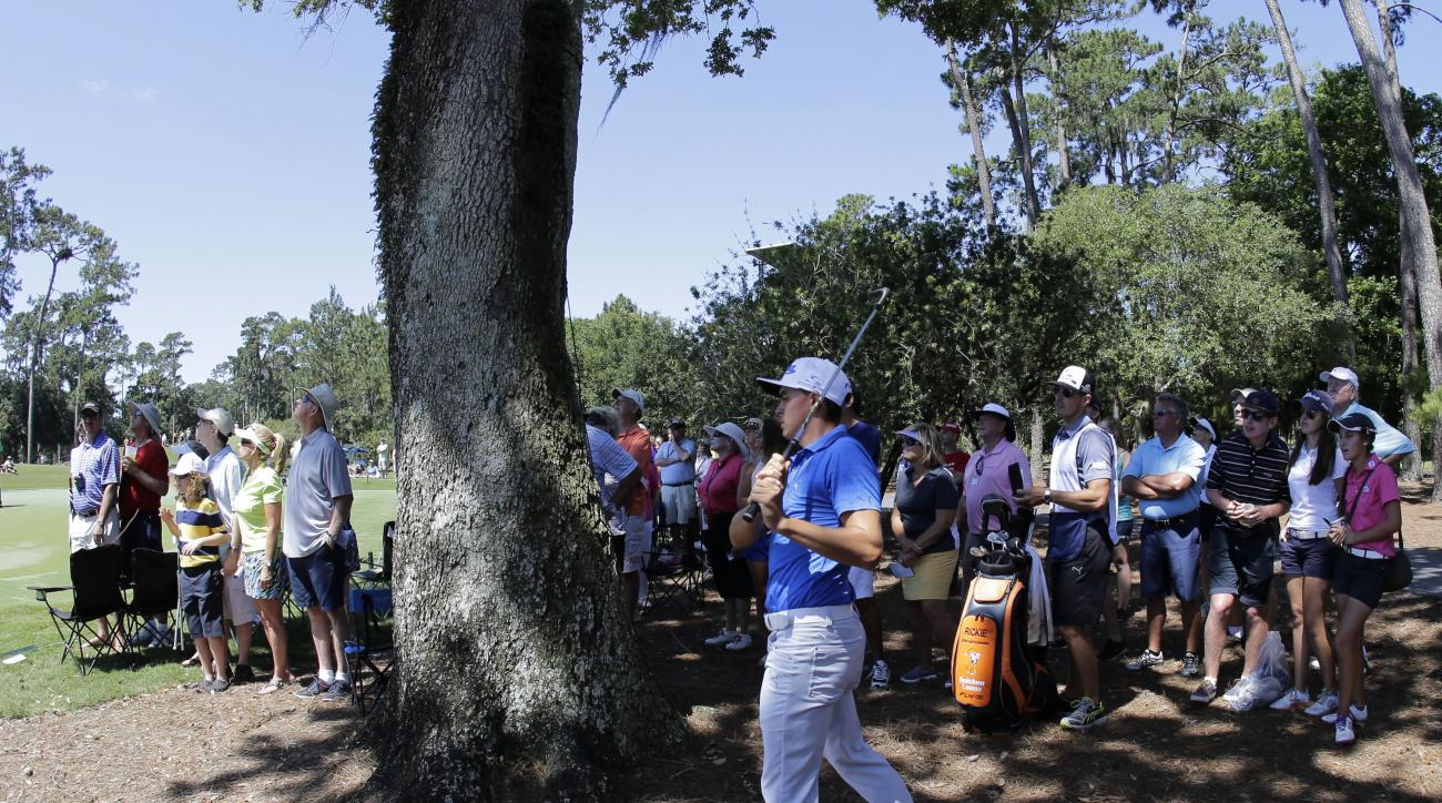 Rickie Fowler follows his shot from behind a tree off the third hole during the first round of The Players Championship golf tournament Thursday, May 7, 2015 in Ponte Vedra Beach, Fla. (AP Photo/Chris O'Meara)