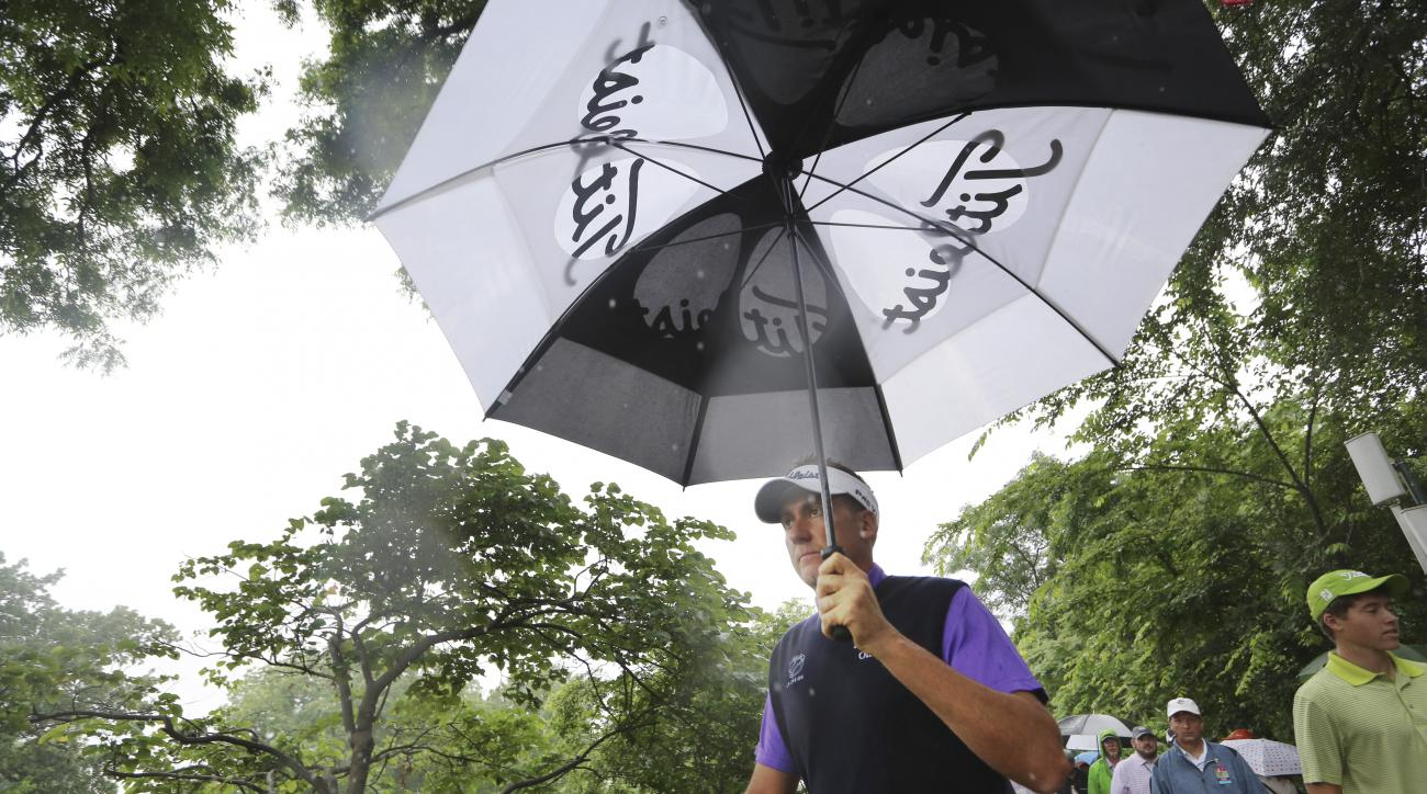 Ian Poulter uses an umbrella while walking the ninth hole during the second round of the Colonial golf tournament, Friday, May 22, 2015, in Fort Worth, Texas. (AP Photo/LM Otero)