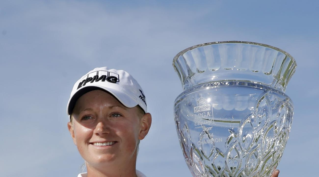 Stacy Lewis holds up the trophy after winning the ShopRite LPGA Classic golf tournament in Galloway Township, N.J., Sunday, June 1, 2014. Lewis shot 16-under-par, 197 to win the tournament. (AP Photo/Mel Evans)