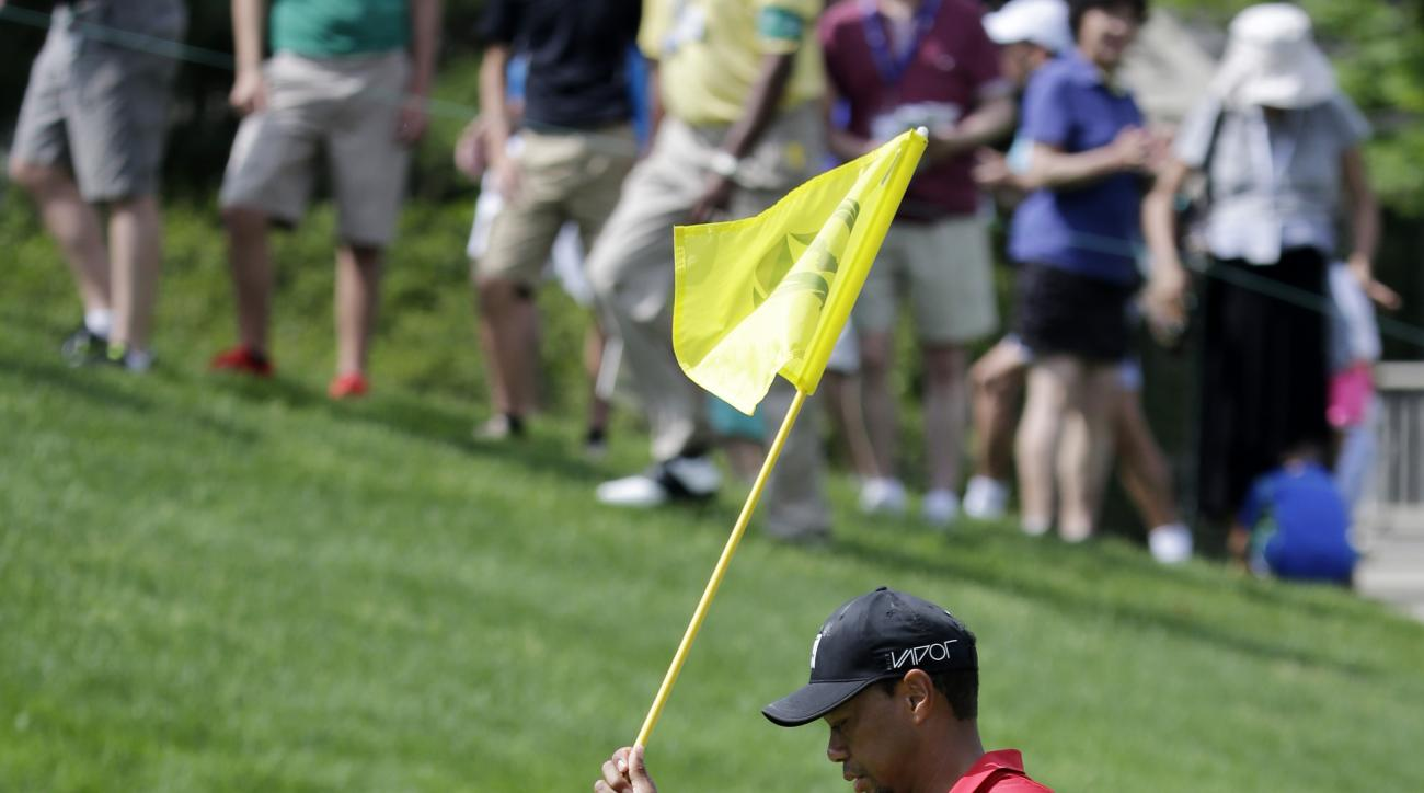 Tiger Woods places the flag stick back in the hole after making a bogie on the 17th hole during the final round of the Memorial golf tournament Sunday, June 7, 2015, in Dublin, Ohio. (AP Photo/Darron Cummings)