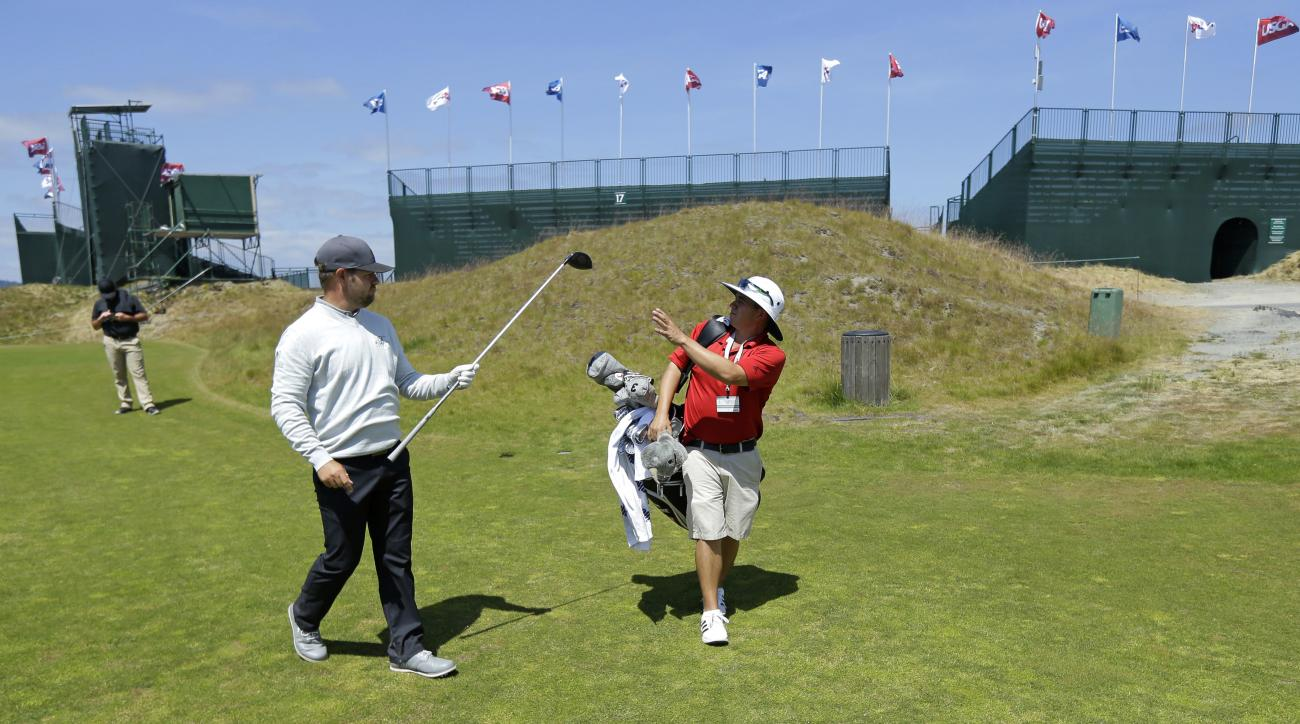 Ryan Moore, left, of Puyallup, Wash., hands a club to Brandon Solomonson, right, a caddie at Chambers Bay golf course, Thursday, June 11, 2015, as he walks off the 18th tee during a practice round in University Place, Wash. Moore will be competing as Cham
